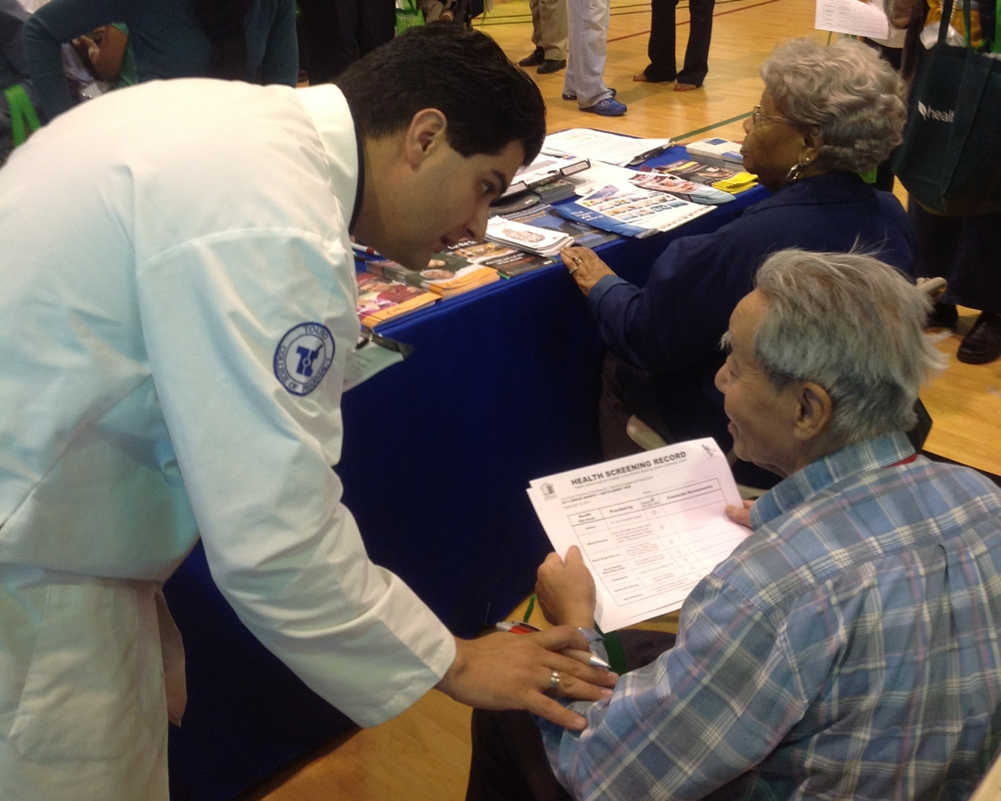 Touro College of Pharmacy student works with a senior at the New York City Housing Authority's 9th Annual Senior Benefit and Entitlement Fair.